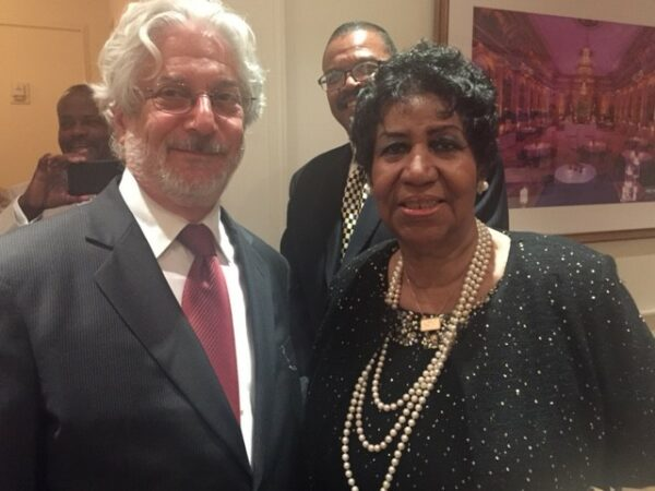A white haired man with a suit stands next to a black haired woman in a dress
