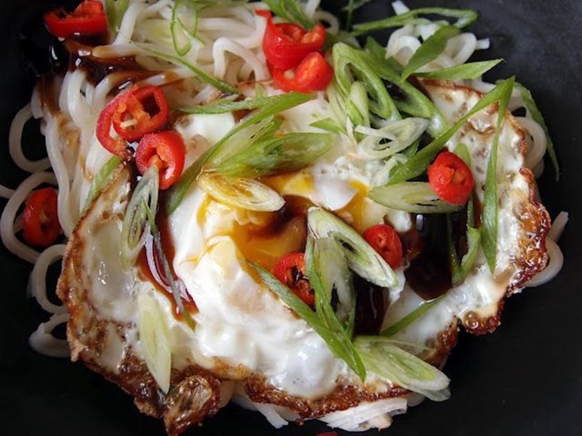 Crispy Thai style fried egg garnished with red birdseye chilies and green scallions